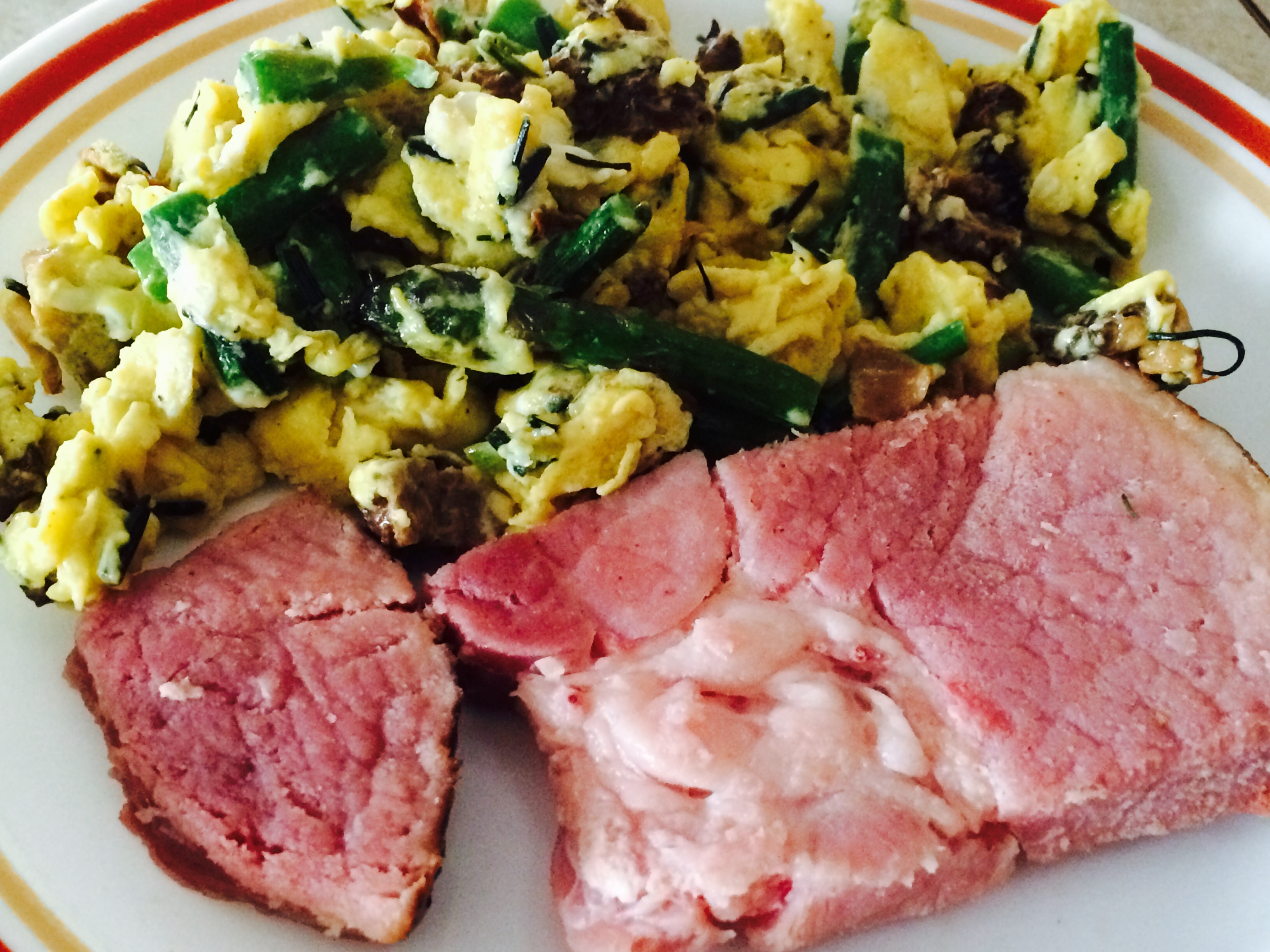 Closeup of ham and eggs scrambled with wild asparagus, wold onions and morel mushrooms from last year's harvest.